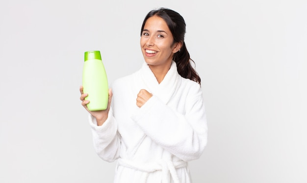 Young hispanic woman feeling happy and facing a challenge or celebrating wearing bathrobe and holding a shampoo