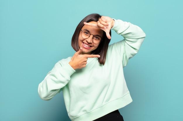 幸せで、友好的で、前向きで、笑顔で、手で肖像画やフォトフレームを作る若いヒスパニック系女性