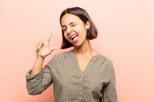 幸せ、楽しさ、自信、前向きで反抗的な感じ、手で岩や重金属のサインを作る若いヒスパニック系女性