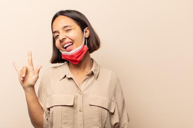 幸せ、楽しさ、自信、前向きで反抗的な感じ、手で岩や重金属の看板を作る若いヒスパニック系女性