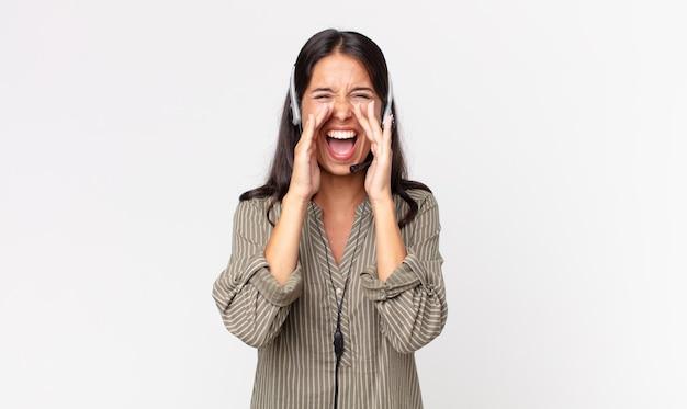 젊은 히스패닉계 여성이 헤드셋을 들고 입 옆에 손을 대고 큰 소리로 외치고 있습니다. 텔레마케팅 개념