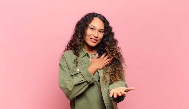 Young hispanic woman feeling happy and in love, smiling with one hand next to heart and the other stretched up front