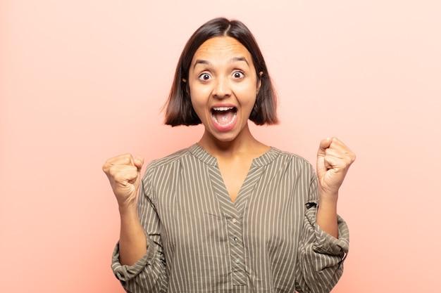 Молодая латиноамериканская женщина чувствует себя счастливой, позитивной и успешной, празднует победу, достижения или удачу