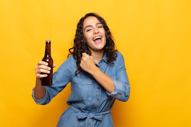 도전에 직면하거나 좋은 결과를 축하 할 때 행복하고, 긍정적이고, 성공하고, 동기 부여 된 젊은 히스패닉 여성