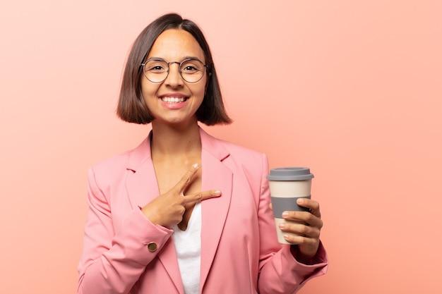 Молодая латиноамериканская женщина чувствует себя счастливой, позитивной и успешной, с рукой делает v-образную форму над грудью, показывая победу или мир