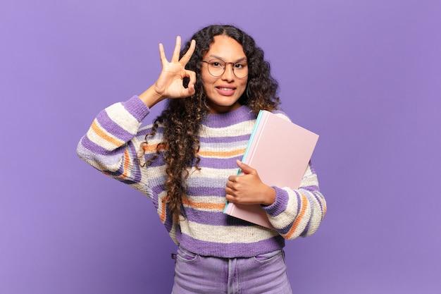행복 하 고 편안 하 고 만족 느낌, 괜찮아 제스처와 승인을 보여주는 젊은 히스패닉 여자 웃 고. 학생 개념