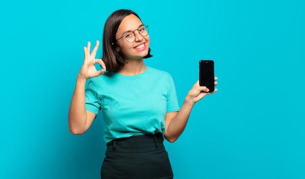 행복하고 편안하고 만족감을 느끼고, 괜찮은 제스처로 승인을 보여주는 젊은 히스패닉계 여성, 미소