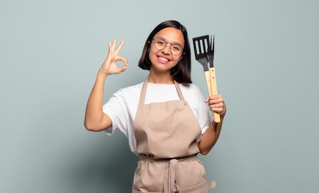 Молодая латиноамериканская женщина чувствует себя счастливой, расслабленной и удовлетворенной, демонстрирует одобрение жестом, улыбаясь