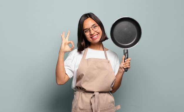 Young hispanic woman feeling happy, relaxed and satisfied, showing approval with okay gesture, smiling