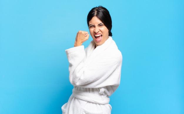 Молодая латиноамериканка чувствует себя счастливой, удовлетворенной и сильной, сгибает фигуру и мускулистые бицепсы, выглядит сильной после тренажерного зала. халат концепция