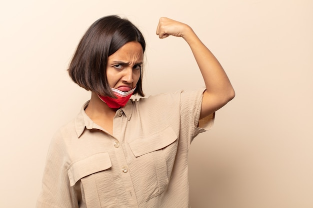 젊은 히스패닉 여성이 행복하고 만족스럽고 강력한 느낌, 유연한 착용감과 근육질 팔뚝, 체육관 후 강하게 보입니다.
