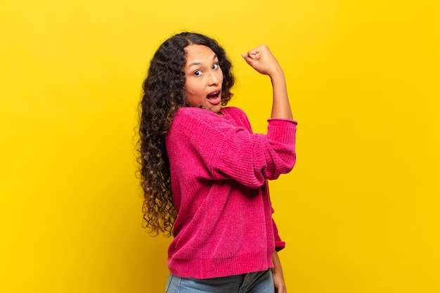 ヒスパニック系の若い女性は、幸せで、満足していて、パワフルで、体を曲げて、筋肉の上腕二頭筋を感じ、ジムの後で強く見えます
