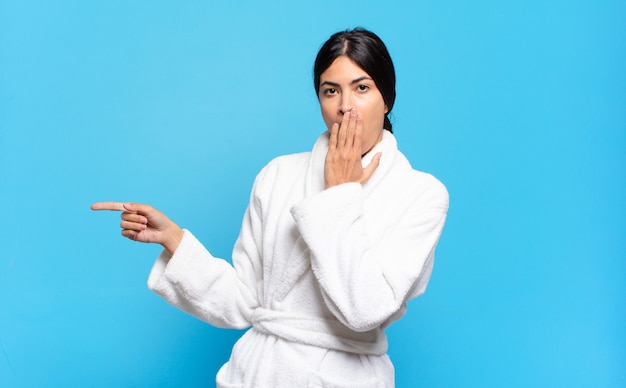 Young hispanic woman feeling happy, shocked and surprised, covering mouth with hand and pointing to lateral copy space. bathrobe concept