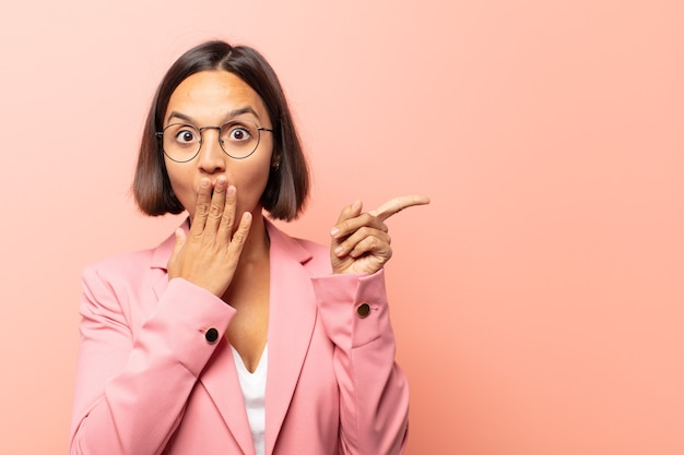 Young hispanic woman feeling happy, shocked and surprised, covering mouth with hand and pointing to lateral copy space