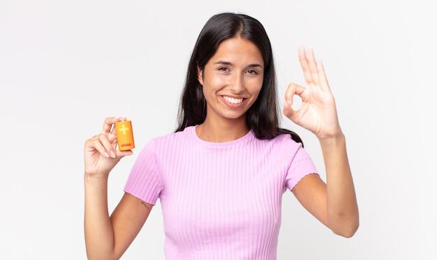 幸せを感じ、大丈夫なジェスチャーで承認を示し、電池を保持している若いヒスパニック系女性