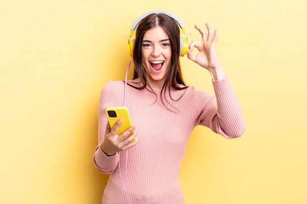 幸せを感じて、大丈夫なジェスチャーで承認を示す若いヒスパニック系の女性。ヘッドフォンと電話のコンセプト
