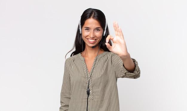 헤드셋으로 괜찮은 제스처로 승인을 보여주는 젊은 히스패닉 여성. 텔레마케팅 개념