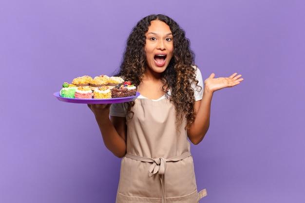 젊은 히스패닉 여자는 행복하고 놀라움과 쾌활한 느낌, 긍정적 인 태도로 웃고 솔루션이나 아이디어를 실현합니다. 요리 케이크 개념