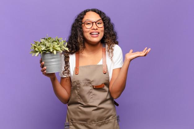 Молодая латиноамериканская женщина чувствует себя счастливой, удивленной и веселой, улыбается с позитивным настроем, реализует решение или идею. концепция садовника