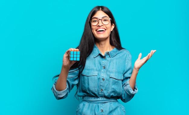 젊은 히스패닉 여성은 행복하고 놀라고 쾌활하며 긍정적인 태도로 웃고 해결책이나 아이디어를 깨닫습니다. 지능 문제 개념