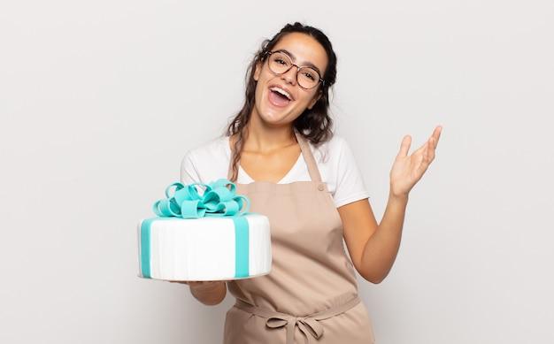 Молодая латиноамериканская женщина чувствует себя счастливой, удивленной и веселой, улыбается с позитивным настроем, реализует решение или идею