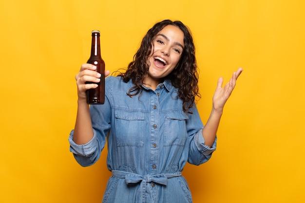 幸せ、驚き、陽気を感じ、前向きな姿勢で笑って、解決策やアイデアを実現する若いヒスパニック系女性