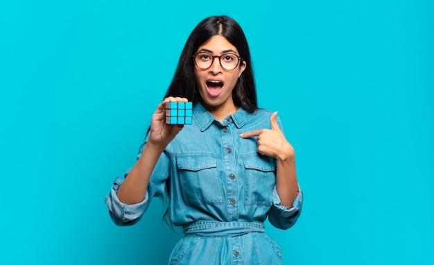 젊은 히스패닉계 여성은 행복하고 놀라고 자랑스러워하며 흥분되고 놀란 표정으로 자신을 가리키고 있습니다. 지능 문제 개념