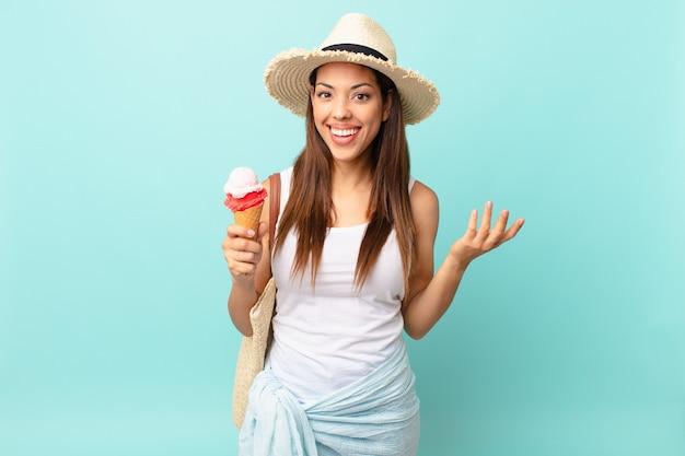 Молодая латиноамериканская женщина чувствует себя счастливой, удивленной, осознавая решение или идею и держа мороженое. концепция шумер