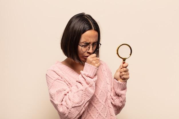 인후통과 독감 증상으로 아픈 젊은 히스패닉 여성, 입으로 덮은 기침