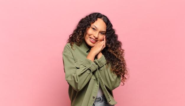 Молодая латиноамериканская женщина чувствует себя влюбленной и выглядит милой, очаровательной и счастливой, романтически улыбается, положив руки на лицо