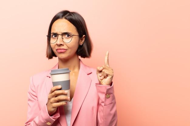 Молодая латиноамериканка чувствует себя гением, гордо подняв палец вверх, после того, как реализовала отличную идею и говорит: «эврика»