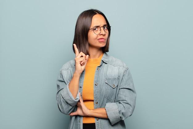 '유레카'라고 말하며 좋은 생각을 깨닫고 자랑스럽게 손가락을 들고 천재처럼 느껴지는 젊은 히스패닉 여성