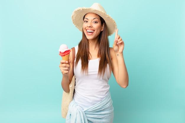 아이디어를 실현하고 아이스크림을 들고 행복하고 흥분된 천재처럼 느끼는 젊은 히스패닉 여성. 여름 개념