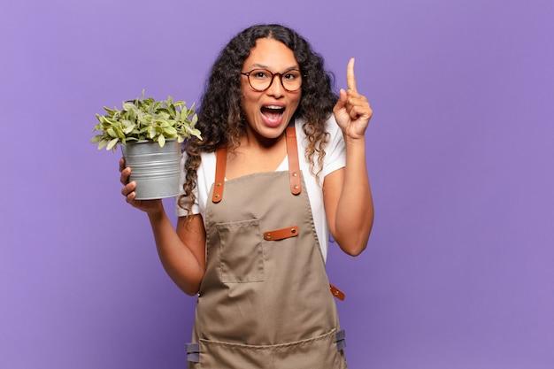 Молодая латиноамериканка почувствовала себя счастливой и взволнованной гением, реализовав идею, весело подняв палец, эврика !. концепция садовника