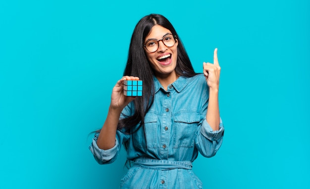 Young hispanic woman feeling like a happy and excited genius after realizing an idea, cheerfully raising finger, eureka!. intelligence problem concept