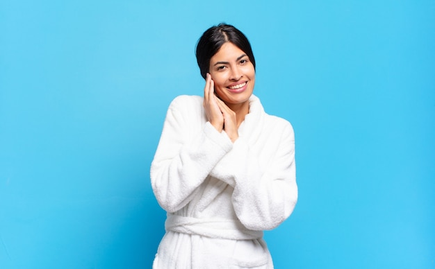 Young hispanic woman feeling in love and looking cute, adorable and happy, smiling romantically with hands next to face. bathrobe concept