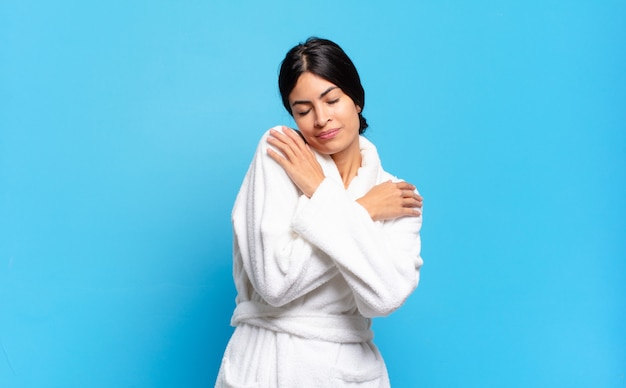 Young hispanic woman feeling in love, smiling, cuddling and hugging self, staying single, being selfish and egocentric. bathrobe concept