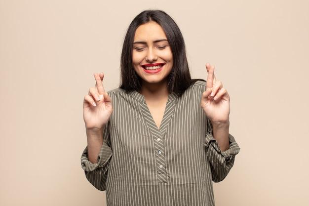 Молодая латиноамериканка нервничает и полна надежды, скрещивает пальцы, молится и надеется на удачу