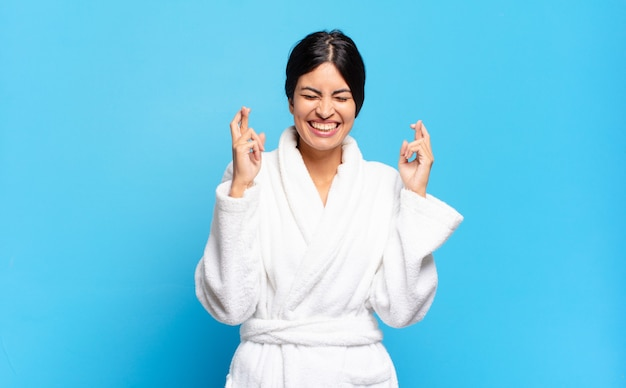 Young hispanic woman feeling nervous and hopeful, crossing fingers, praying and hoping for good luck. bathrobe concept