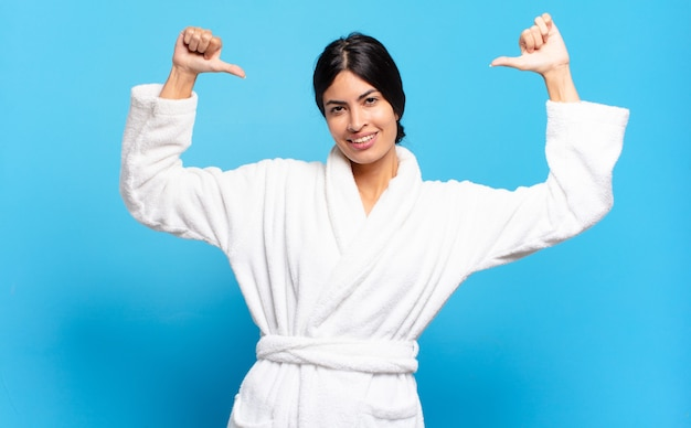 Young hispanic woman feeling proud, arrogant and confident, looking satisfied and successful, pointing to self. bathrobe concept