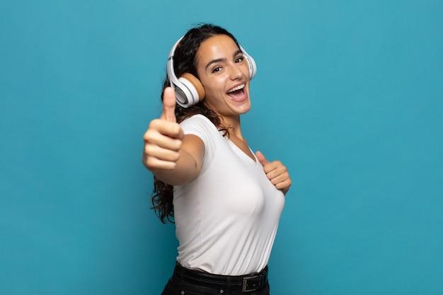 誇り高く、気楽で、自信を持って幸せを感じ、親指を立ててポジティブに微笑むヒスパニック系の若い女性