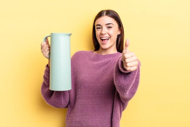誇らしげに感じ、親指を立てて前向きに笑っている若いヒスパニック系女性。コーヒー魔法瓶のコンセプト