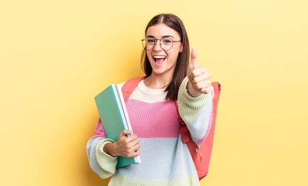 젊은 히스패닉계 여성이 자랑스러워하고 엄지손가락을 치켜세우며 긍정적으로 웃고 있습니다. 학생 개념
