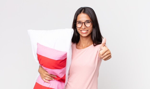 Young hispanic woman feeling proud,smiling positively with thumbs up wearing pajamas and holding a pillow