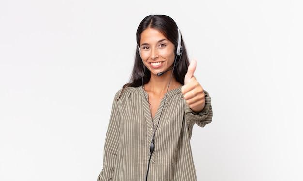 헤드셋을 들고 엄지손가락을 치켜세우며 긍정적으로 웃고 있는 젊은 히스패닉 여성. 텔레마케팅 개념
