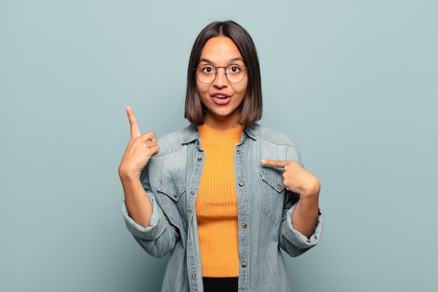 Young hispanic woman feeling proud and surprised, pointing to self confidently, feeling like successful number one