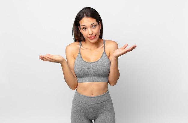 Молодая латиноамериканская женщина чувствует себя озадаченной, сбитой с толку и сомневающейся. фитнес-концепция