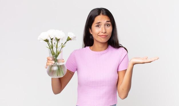 젊은 히스패닉계 여성은 어리둥절하고 혼란스러워하며 장식용 꽃을 들고 있는 것을 의심합니다