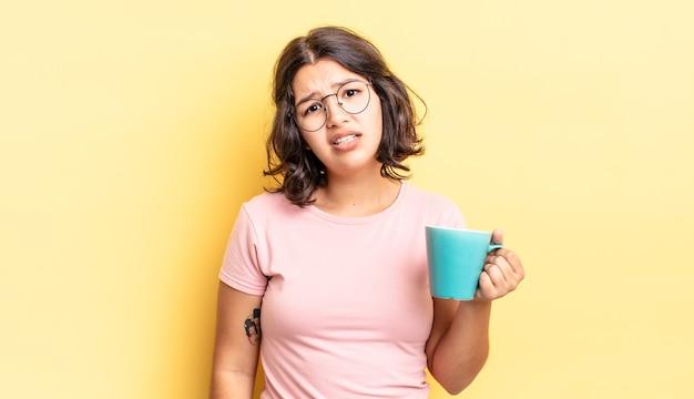 困惑と混乱を感じている若いヒスパニック系女性。コーヒーマグのコンセプト
