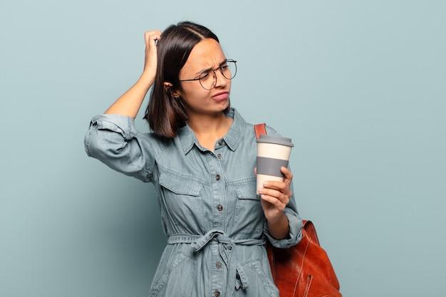 Молодая латиноамериканская женщина чувствует себя озадаченной и сбитой с толку, почесывает голову и смотрит в сторону